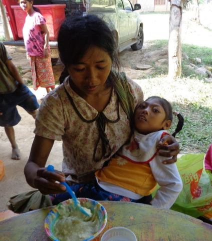 Photograph taken by Gene Long, Joy being fed by her mother on a visit to the Yellow Leaf tribe
